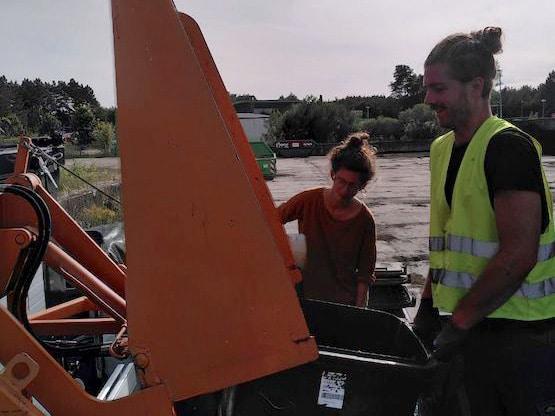 Zwei Menschen beim Tonnen entleeren auf Kompostieranlage